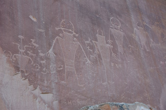 Five human-like figures pecked into stone, with smaller images, including bighorn sheep, interspersed between them, on reddish brown rock.