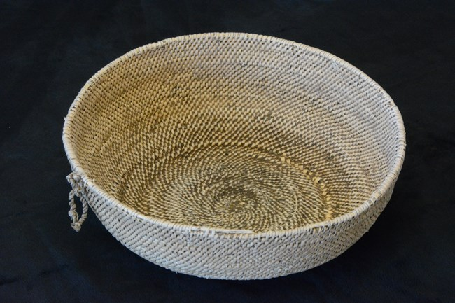 Round, woven, tan colored basket on a black background.