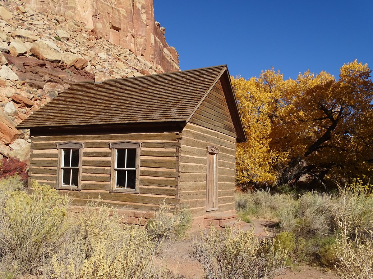 Log cabin building with stone foundation, in front of red cliffs, yellow trees, and blue sky.