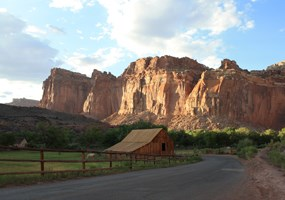 historic Gifford (Pendelton) Barn with sunlit red cliffs in the background