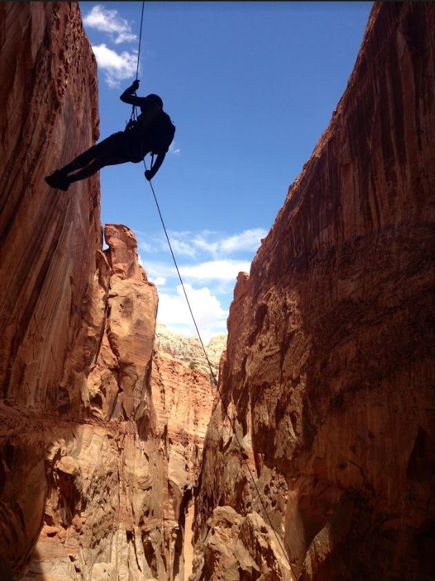 A person rappelling into a canyon