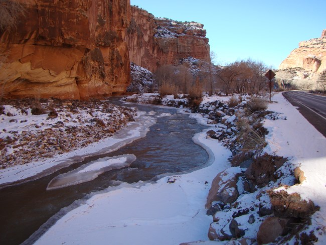 Small river with ice along the edges and in the center, and snow on the riverbanks, below red cliffs and blue sky, with a road to the right of the river.