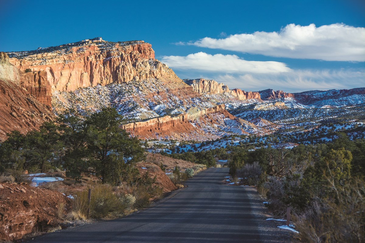 Blacktop road with small green trees and shrubs and red cliffs covered in snow, with blue sky and clouds above.