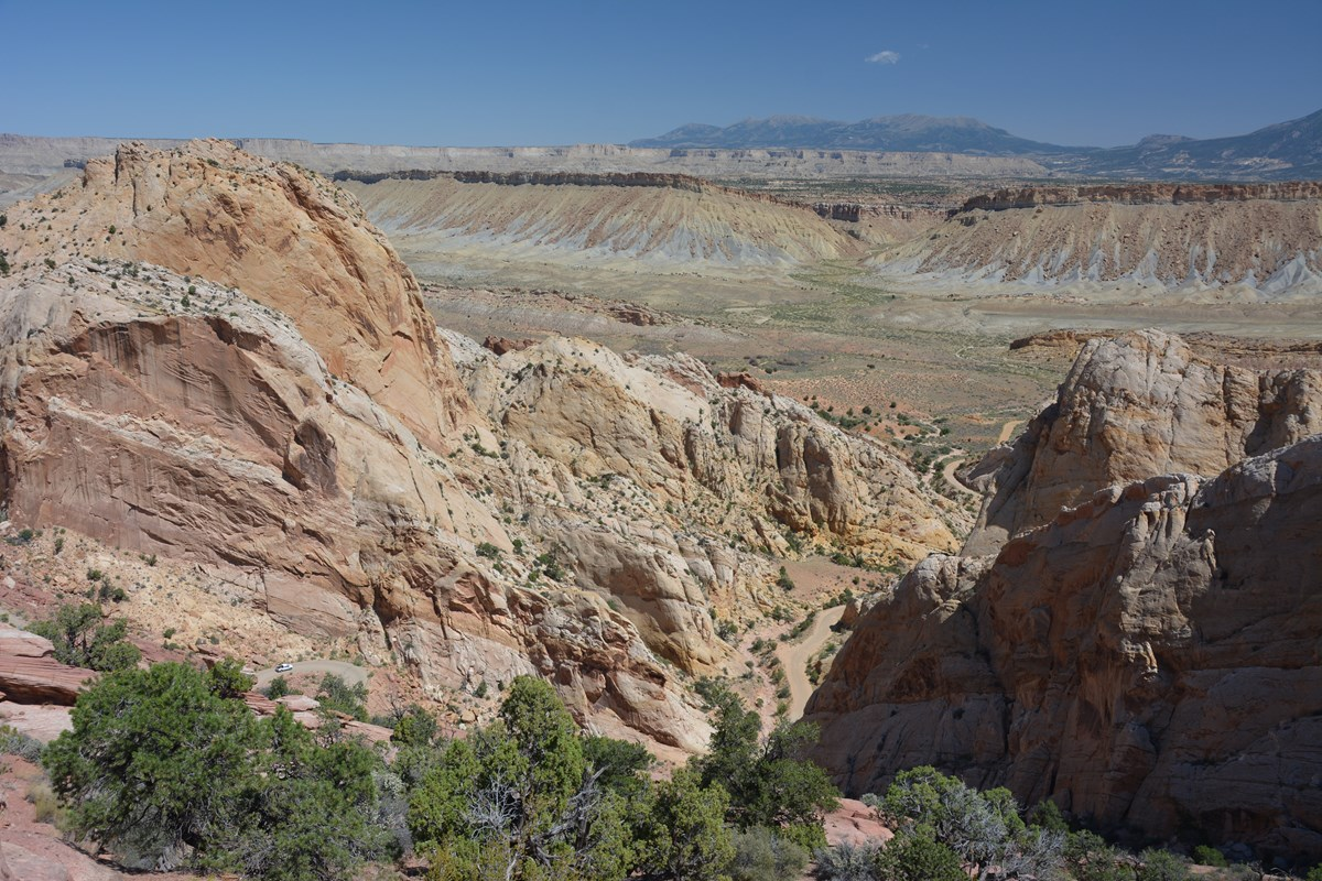 Panoramic view of rock cliffs, some trees, a dirt road, and mountains in the distance, with blue sky.