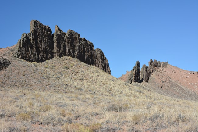 long line of jagged black rocks rising out of eroding red hills with blue sky above.
