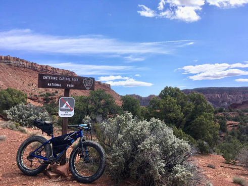 Fat tire bike leaning against wooden sign with scenic red cliffs and blue skies in the background.
