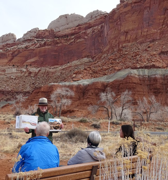 Ranger in flat hat, holding photos and diagrams up in front of audience of three people, with a background of colorful rock layers and formations.