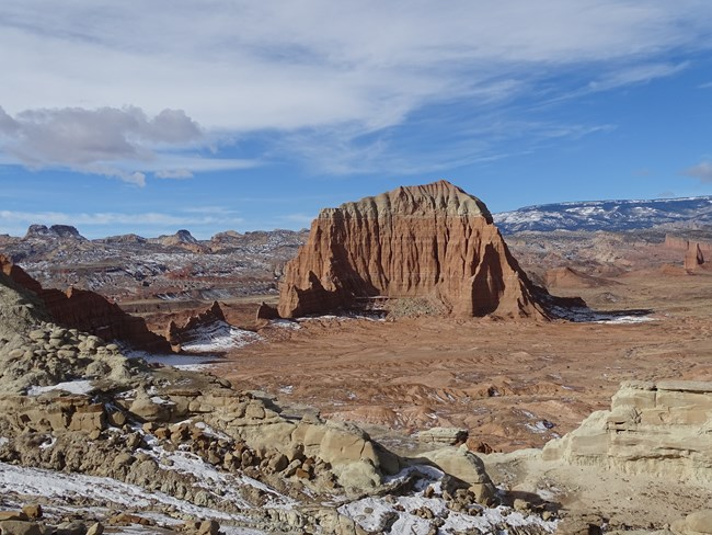 Large orange monolith with colorful rock cliffs surrounding the valley it is in, with blue sky, clouds, and a bit of snow.