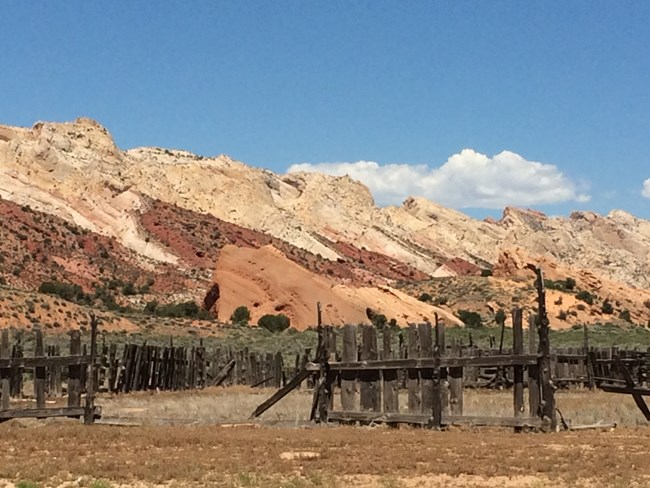 Old, deteriorating wooden fence with colorful rock cliffs and blue sky behind.