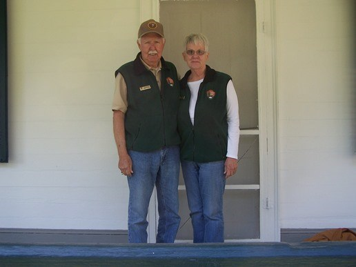 Park volunteers Don and Pat Curtis standing on the porch of the Doctor's Cottage at Oakland.