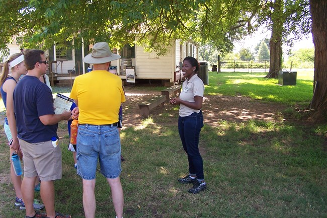 HBCUI Intern Daysha Brown talks with visitors outside the Oakland Plantation Store.