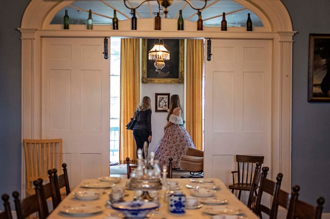 A member of the Prud'homme Family in period dress talks with a visitor in the parlor.