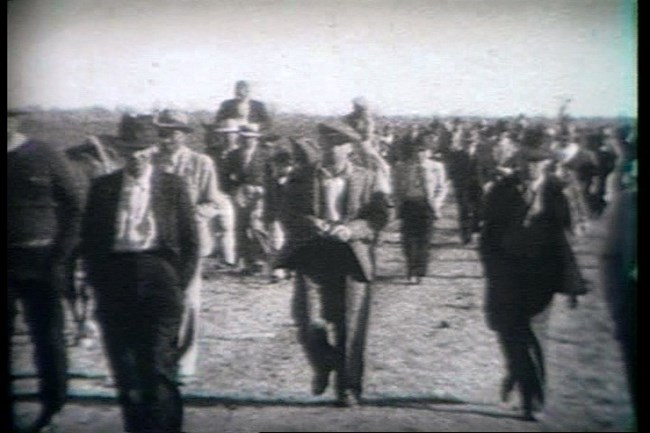 Black and white historic image of gentlemen dressed in suits and hats walking on a dirt road to the Magnolia Horse races.