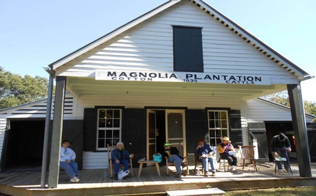Visitors eat lunch while sitting in rocking chairs on the front porch of Magnolia Store.