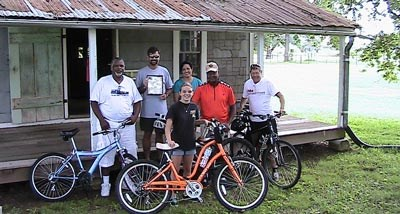 Bike Riders posing in front of Oakland's tenant cabin.