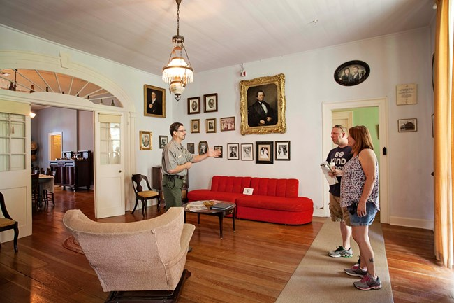 Ranger Rodney Meziere talks with visitors in the parlor of the Oakland Main House