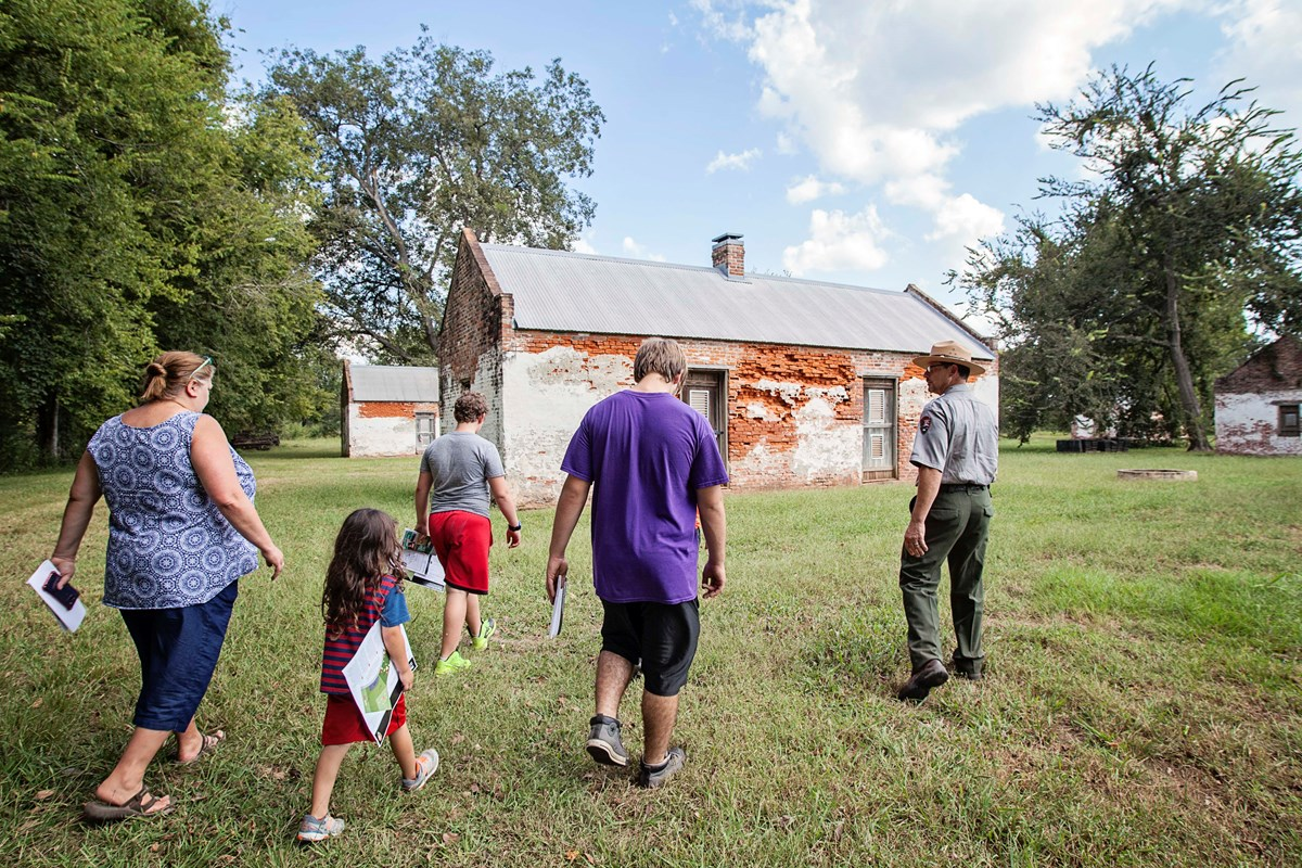 Ranger Rodney Meziere walks with visitors to the brick slave/tenant cabins at Magnolia Plantation