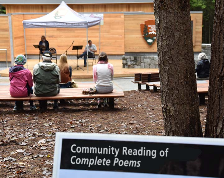 Visitors sit in audience listening to people read from Carl Sandburg's Complete Poems