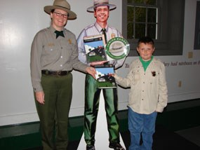 Park Ranger stands with the first Junior Ranger in the park's history.