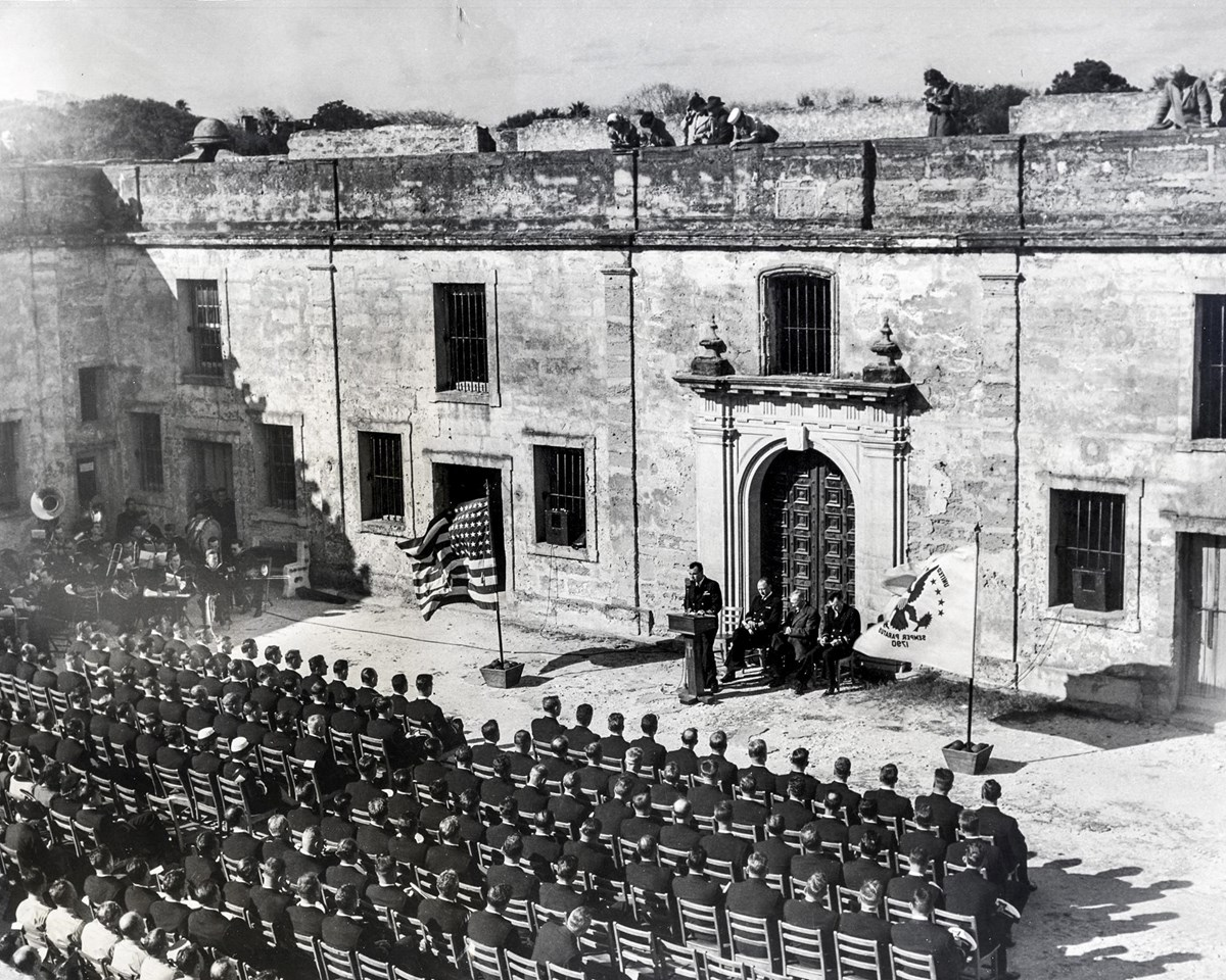 Coast Guardsmen sit in chairs in the Castillo's courtyard for their graduation ceremony.