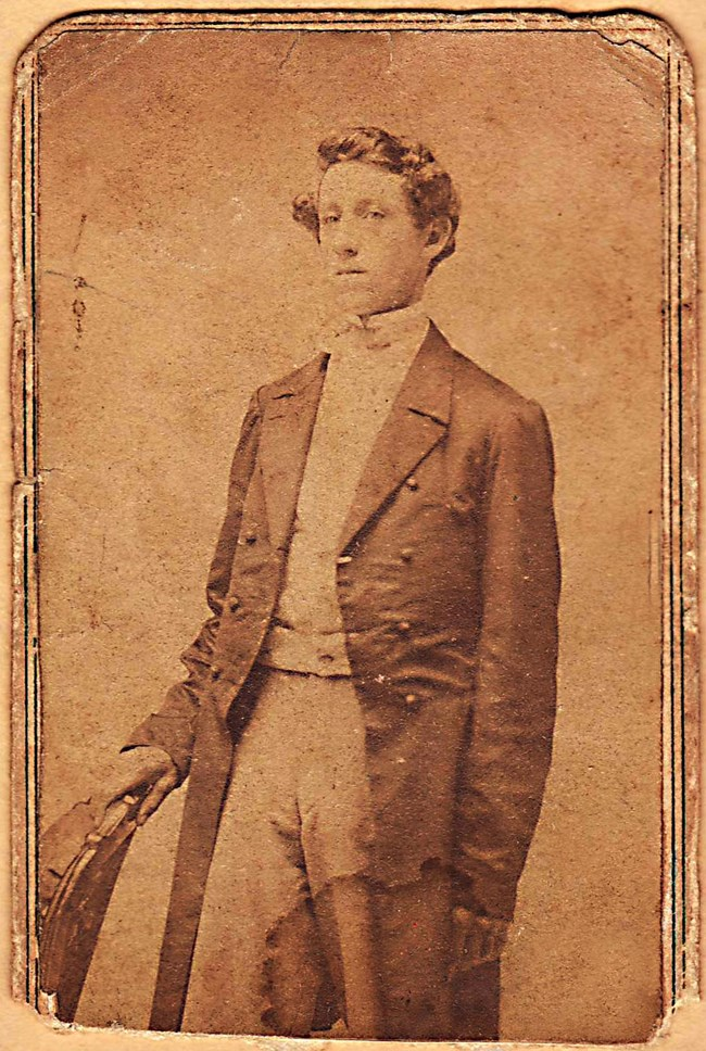 Sepia toned portrait of a young man named Elias Peck dressed in a coat