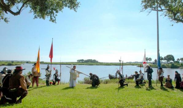 Conquistadors bearing flags watch as Pedro Menendez kisses the foot of a cross.