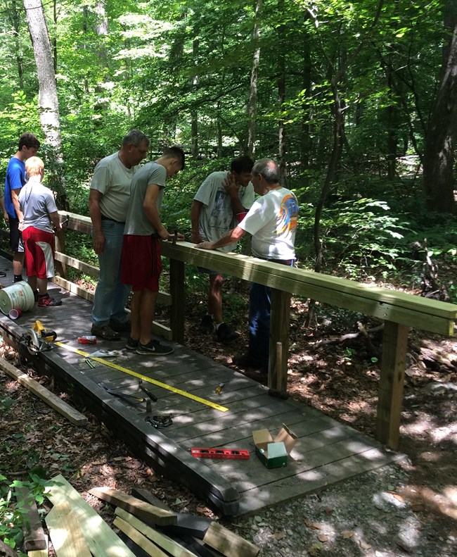Scouts installing railing onto wooden boardwalk