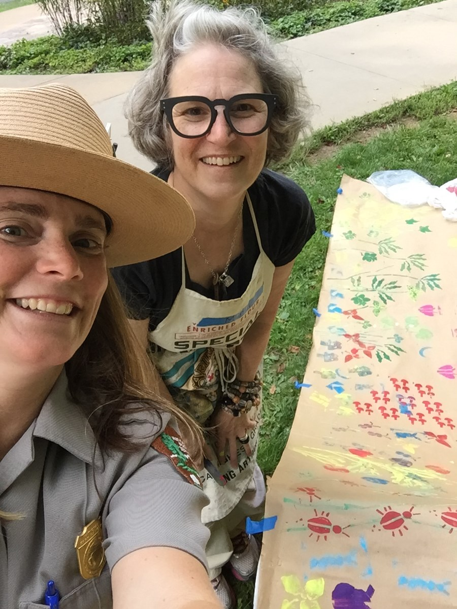 Two women, one in ranger uniform, behind a table covered in brown paper with multicolored stamps.