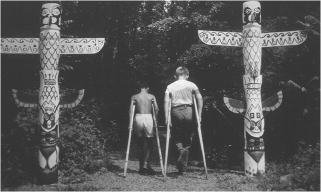 2 Boys on crutches walk between 2 totem poles