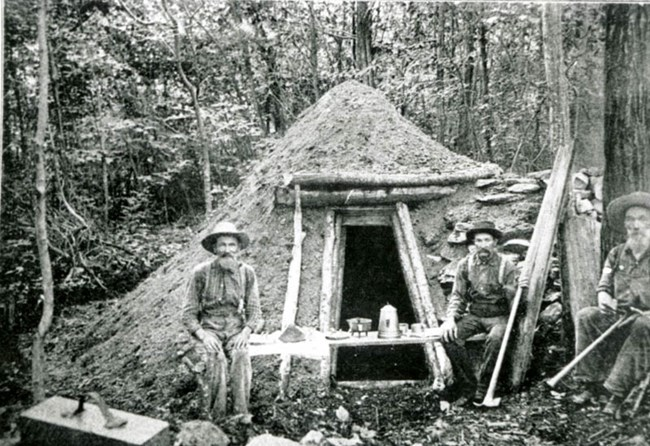 Historical photograph of three colliers sitting next to their hut made of sticks.