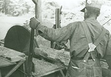 A CCC worker operates a saw to create lumber. He is seen using the machine to split a log in half.