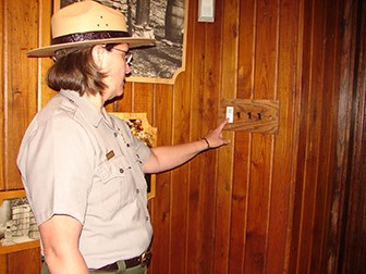 NPS Ranger turning off LED light switch in the exhibit located in the visitor center