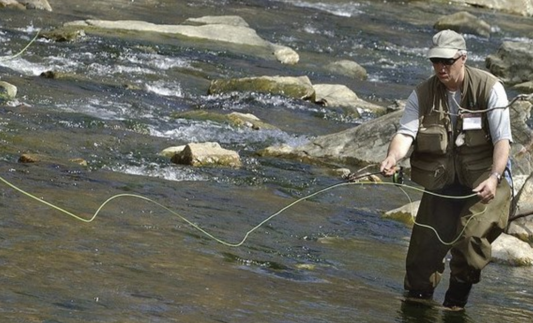 Fly fisherman in waders casting in creek