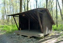 Wooden, 3-sided shelter with roof, located in the woods.
