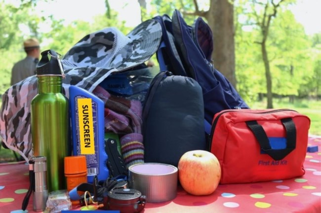 Hiking essentials such as food, first aid kit, water, and sun protection