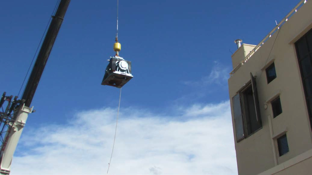 Photo of crane hoisting new elevator motor