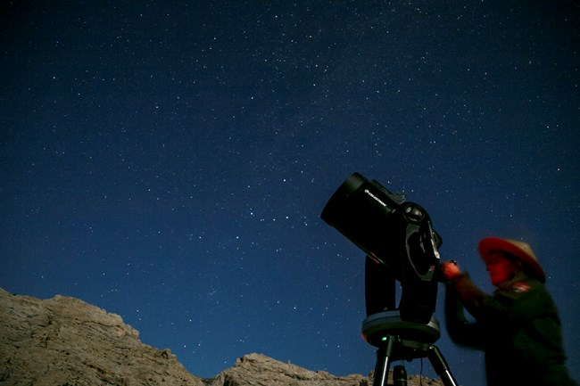 Park ranger adjusts telescope against a starry sky background