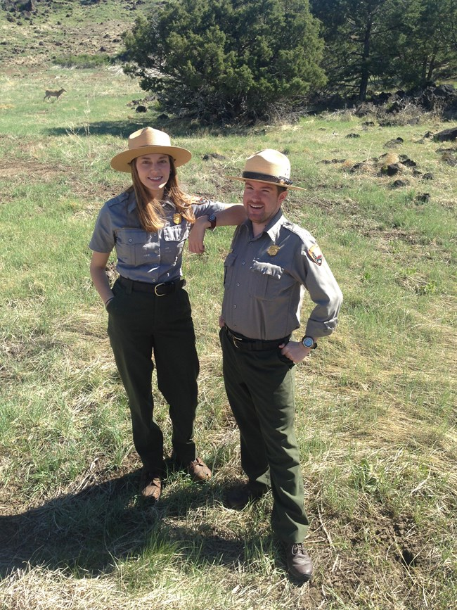 A female and male park ranger stand in a grassy area on a sunny day.  The female ranger on left rests her elbow on the male ranger's shoulder to the right.  They both smile facing the camera.  A deer in the right background makes its way toward the trees.