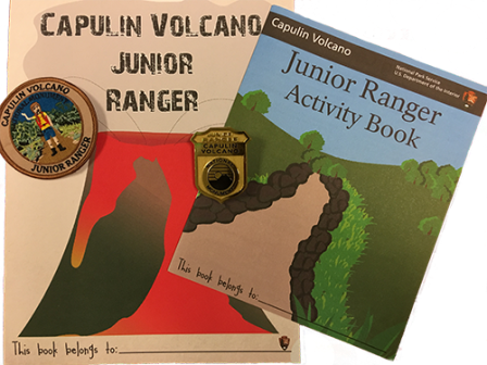 Two Junior Ranger books side by side with a round patch and plastic badge.