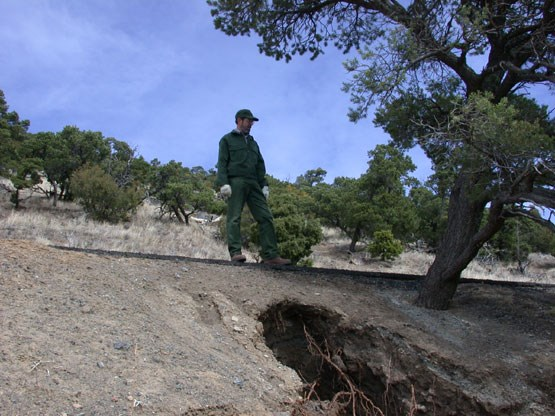 color photograph of park service staff examining eroding gully by volcano road