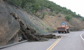 color photograph of front end loader clearing rock slide on road