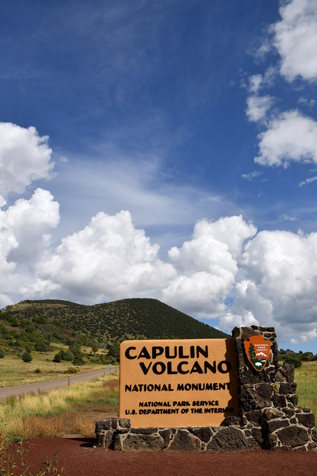 "An entrance made of lava rock has states ""Capulin Volcano National Monument, National Park Service, Department of the Interior"".  The sign also includes the National Park Service Arrowhead Logo.  The sign sits in the foreground of a forested volcano."