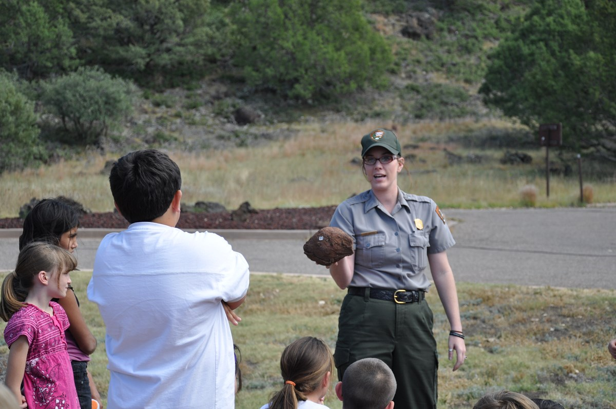 A park ranger is giving a presentation.  She stands facing the camera while holding a rock outward toward a group of five children who are focused on her explanation.  The ranger is wearing a classic ballcap, button-up shirt with name tag and badge.