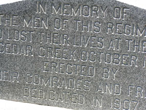 Closeup picture of part of a stone monument with block print engraving.