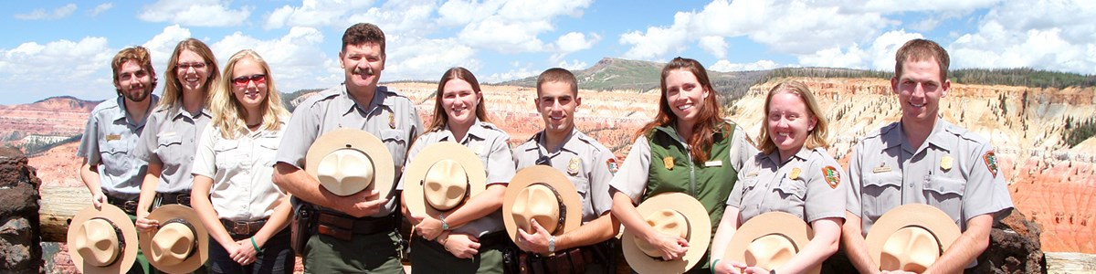 Group of park employees in NPS Uniform standing in front of red and orange cliffs.