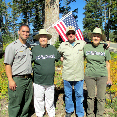 Park employee and three elderly volunteers standing in front of an american flag.