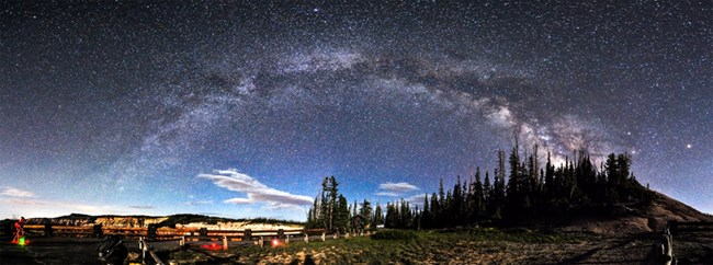An arch of glittering stars over trees and red cliffs, with telescopes in the foreground.
