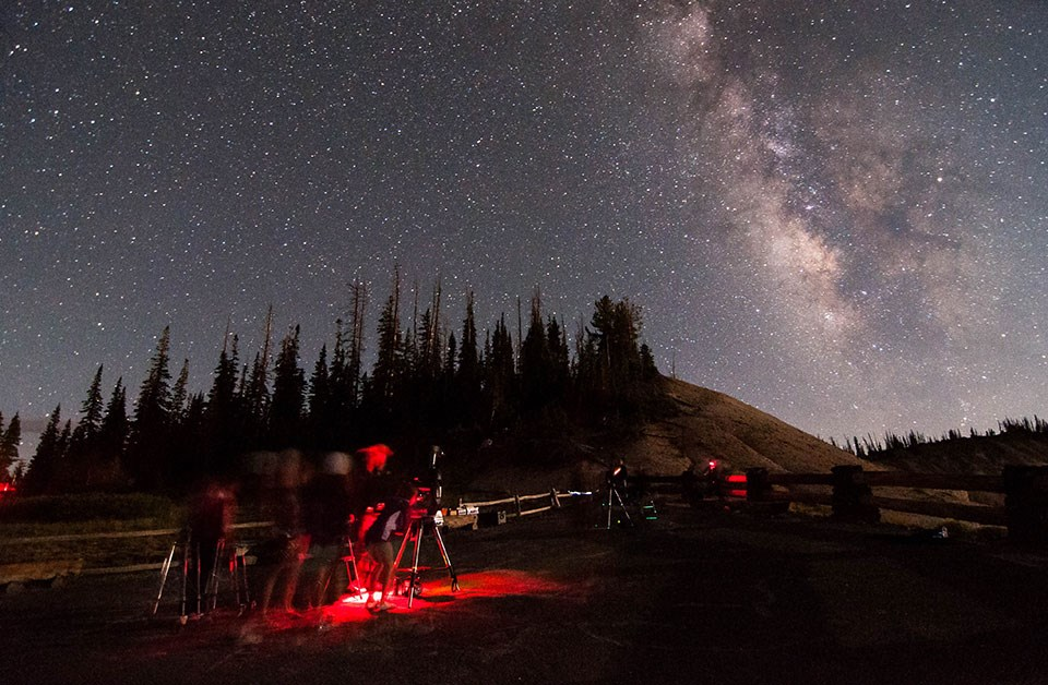 Dark starry skies over people looking through telescopes lit up by red lights.