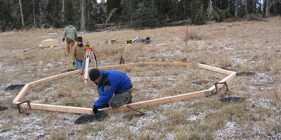 Volunteer employee assembling wooden parts of the yurt foundation.
