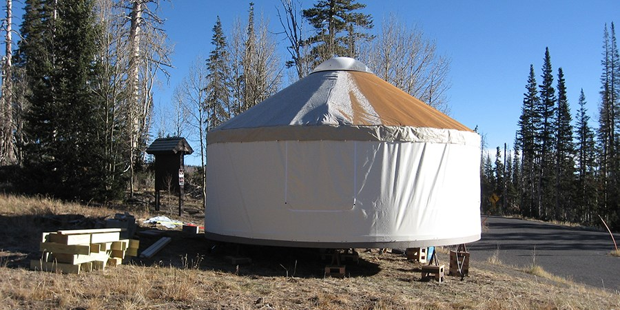 The yurt fully assembled with vinyl roof and walls.